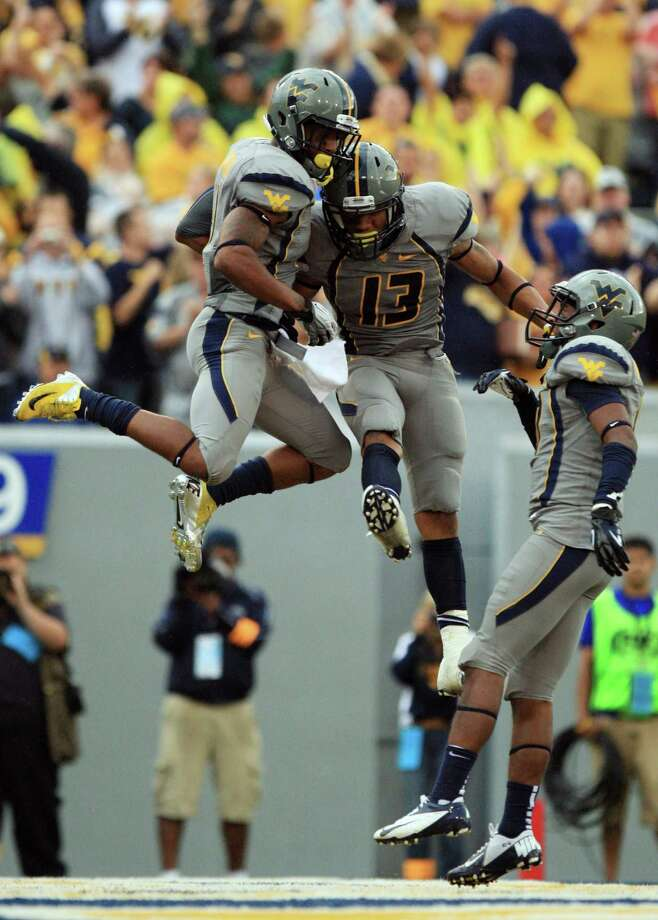 West Virginia players, from left, Tavon Austin, Andrew Buie and Stedman Bailey celebrate Austin's touchdown during an NCAA college football game against the University of Maryland in Morgantown, W.Va., Saturday, Sept. 22, 2012. (AP Photo/Christopher Jackson) Photo: Christopher Jackson