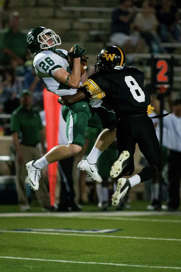 Stratford wide receiver Graham Jones (26) makes a leaping catch over Spring Woods defensive back Derry Bedford during the first quarter of a high school football game at Darrell Tully Stadium on Friday, Sept. 28, 2012, in Houston. Photo: Andrew Richardson, For The Chronicle / © 2012 Andrew Richardson
