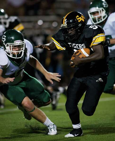 Spring Woods running back Charlie Jones (5) carries the ball during the first quarter of a high scho