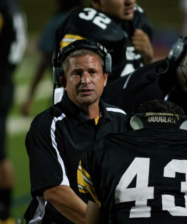 Spring Woods head coach Keith Cripps speaks on the sideline with his players during the first quarter of a high school football game at Darrell Tully Stadium on  Friday, Sept. 28, 2012, in Houston. Photo: Andrew Richardson, For The Chronicle / © 2012 Andrew Richardson