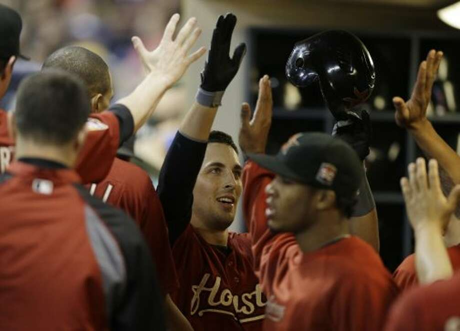 Jason Castro gets high-fives in the dugout after his home run during the fifth inning. (Jeffrey Phelps / Associated Press)