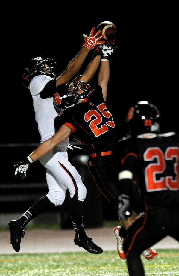 Stamford's Jake Bivona, left, and Ridgefield's Aidan Mauro, right, reach for a pass that fell incomplete during Friday's football game at Ridgefield High School on September 28, 2012. Photo: Lindsay Niegelberg / Stamford Advocate