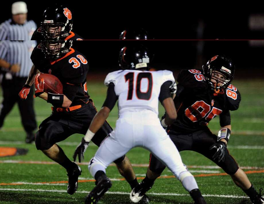 Ridgefield's Samuel Gravitte carries the ball around Stamford's John Pasard during Friday's football game at Ridgefield High School on September 28, 2012. Photo: Lindsay Niegelberg / Stamford Advocate