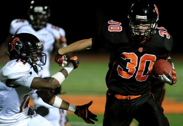 Ridgefield's Samuel Gravitte carries the ball during Friday's football game against Stamford at Ridgefield High School on September 28, 2012. Photo: Lindsay Niegelberg / Stamford Advocate