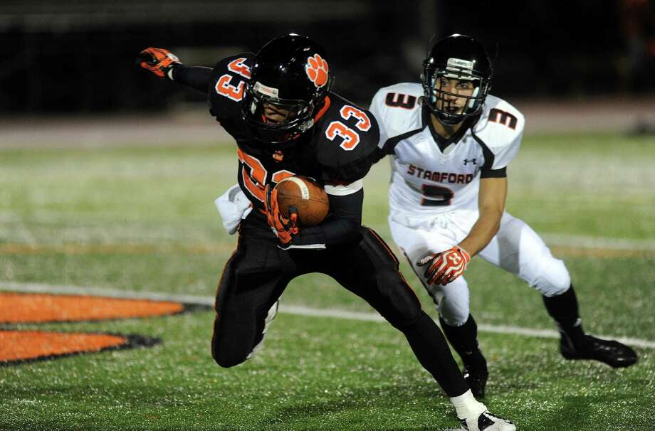 Ridgefield's Bryan Jimenez avoids a tackle from Stamford's Jake Bivona during Friday's football game at Ridgefield High School on September 28, 2012. Photo: Lindsay Niegelberg / Stamford Advocate