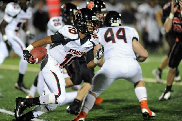 Stamford's John Pasard carries the ball during Friday's football game at Ridgefield High School on September 28, 2012. Photo: Lindsay Niegelberg / Stamford Advocate