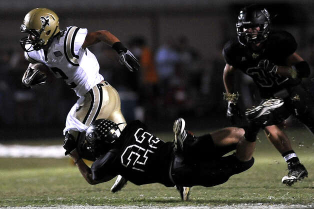 Nederland wide receiver Michael Shaw with a short carry before Vidor player Alex Boutte takes him down at Vidor High School on Friday, September 29, 2012. Photo taken: Randy Edwards/The Enterprise