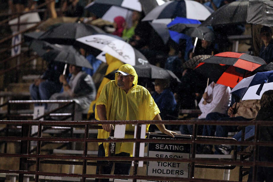 Undaunted by the rain and shielded to a point, Friday night football fans get their fix as Boerne Champion hosts Alamo Heights. Photo: Tom Reel, Express-News / ©2012 San Antono Express-News