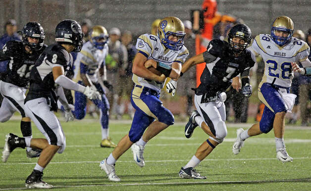 Mules quarterback Kalen Brockwell protects a slippery ball as he runs in the first half as Champion hosts Alamo Heights at Boerne Stadium on September 28, 2012. Photo: Tom Reel, Express-News / ©2012 San Antono Express-News