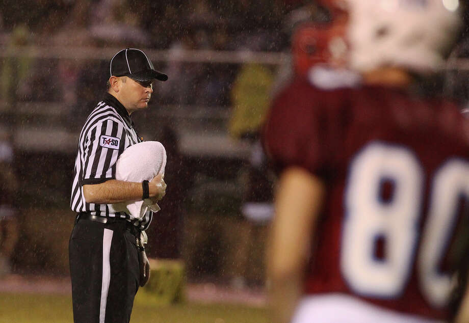 A game official protects the game ball with a towel from the rain before the start of the Antonian-Devine football game at Antonian High School on Friday, Sept. 28, 2012. Photo: Kin Man Hui, Express-News / ©2012 San Antonio Express-News
