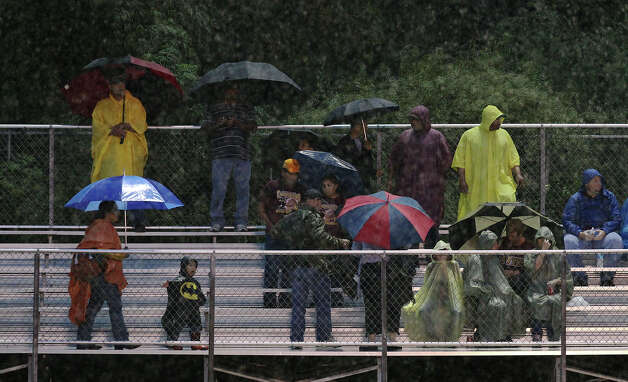 Rain pours on fans attending the Antonian-Devine high school football game at Antonian High School on Friday, Sept. 28, 2012. Photo: Kin Man Hui, Express-News / ©2012 San Antonio Express-News