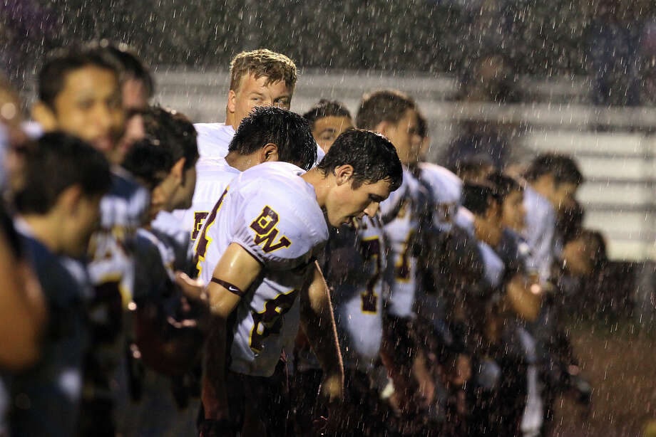 The Devine High School football team gets soaked from the rain during the playing of the National Anthem before the game against Antonian at Antonian High School on Friday, Sept. 28, 2012. Photo: Kin Man Hui, Express-News / ©2012 San Antonio Express-News
