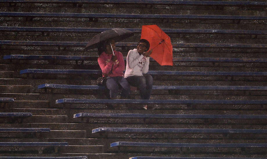 Two fans have a laugh in the stands as they protect themselves from the rain during a high school football game between Brackenridge and Jefferson at Alamo Stadium in San Antonio, Friday, September 28, 2012.