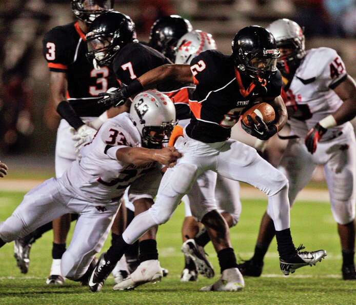 Texas City's Donald Lynch #2 breaks the tackle of Goose Creek's Sean Dre Alexander #33 during  a dis