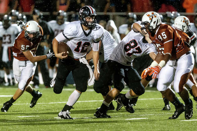 Churchill quarterback Nate Pearson (12) looks for running room as Madison's C.J. Reese (right) closes in during their game at Heroes Stadium on Sept. 28, 2012.  MARVIN PFEIFFER/ mpfeiffer@express-news.net Photo: MARVIN PFEIFFER, Express-News / Express-News 2012