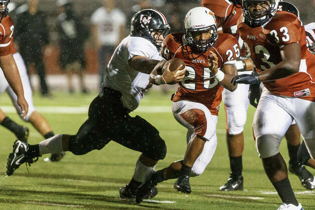 Madison running back Galen McAllister (25) runs past Churchill's Logan Milton during their game at Heroes Stadium on Sept. 28, 2012.  Madison won the game 49-14.  MARVIN PFEIFFER/ mpfeiffer@express-news.net Photo: MARVIN PFEIFFER, Express-News / Express-News 2012