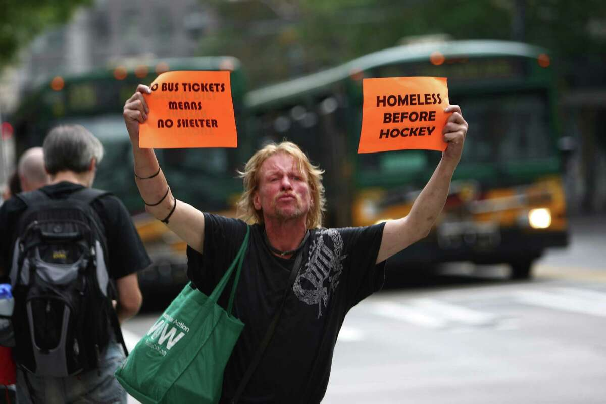 Bus rider Tony Webb holds up signs during a