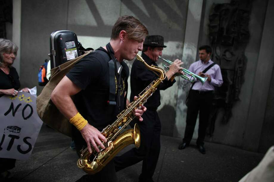 "Members of Tubaluba, including Joseph Sheedy on the sax, march during a ""funeral"" for downtown Seattle's free ride area. Photo: JOSHUA TRUJILLO / SEATTLEPI.COM"