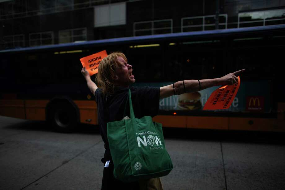 "Bus rider Tony Webb holds up signs during a ""funeral"" for downtown Seattle's free ride area. On September 29th King County Metro's free ride area will end, along with many other service changes. Advocates say the end of the free rides will impact the poor and elderly that use the service. Photo: JOSHUA TRUJILLO / SEATTLEPI.COM"