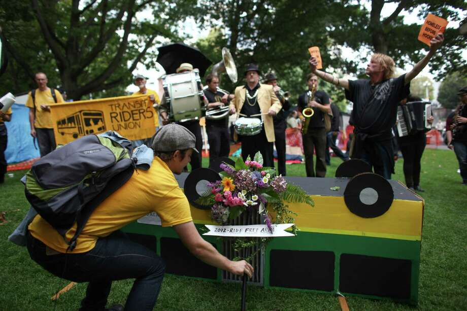 "Flowers are placed next to a cardboard bus during a ""funeral"" for downtown Seattle's free ride area. Photo: JOSHUA TRUJILLO / SEATTLEPI.COM"