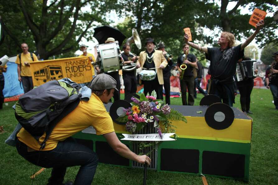 Flowers are placed next to a cardboard bus during a