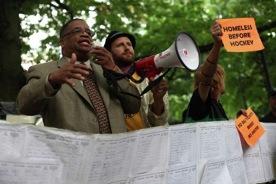 "King County Councilman Larry Gossett speaks as petition signatures are unrolled during a ""funeral"" for downtown Seattle's free ride area. Photo: JOSHUA TRUJILLO / SEATTLEPI.COM"