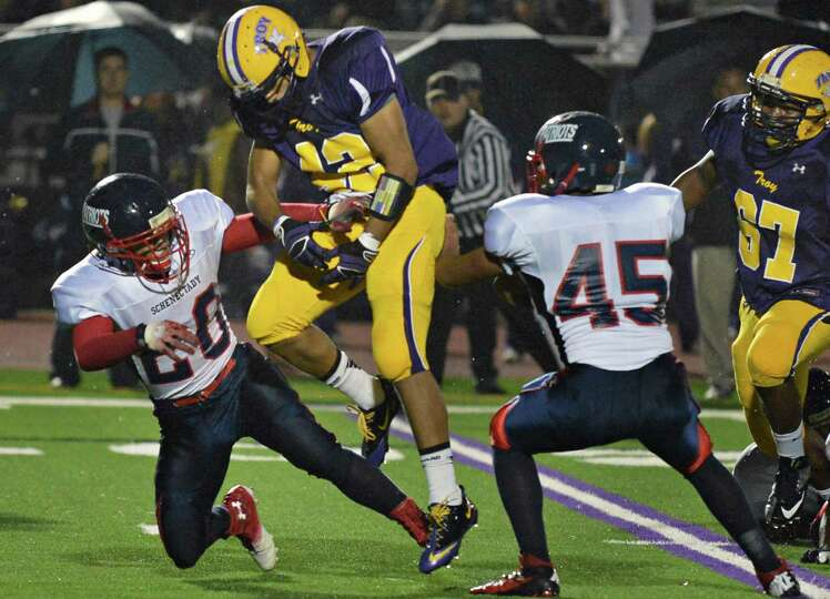 Troy's #42 Victor Priela has the ball stripped away by Schenectady defenders #20 Felix Rodriguez, le