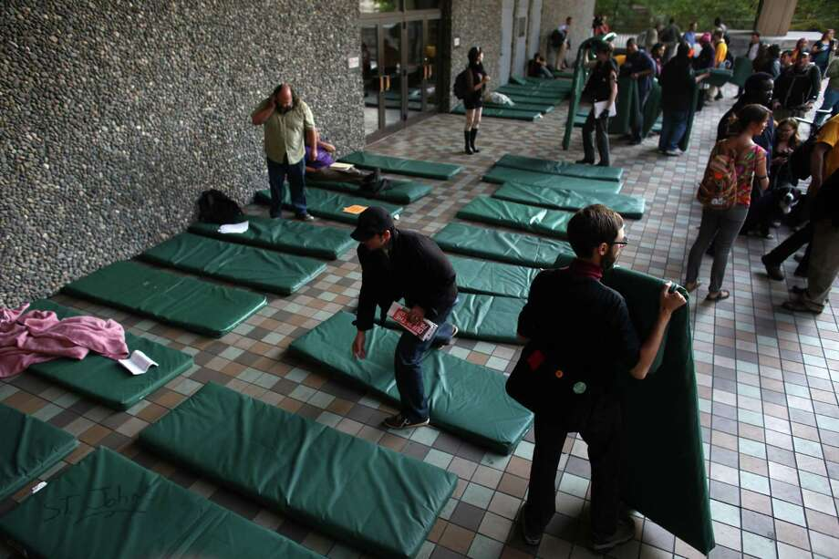 "Homeless people and advocates arrange mats at the King County Administration Building after they held a ""funeral"" for downtown Seattle's free ride area. 