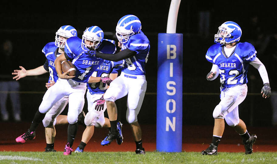 Shaker's Deven Koehler (1), center left, celebrates a touchdown, to make the score 35-0, with teamma