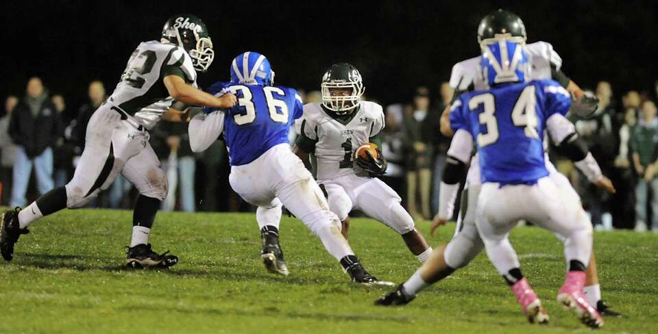 Shenendehowa's Marcelino Christie (1), center, runs the ball during their football game against Shak