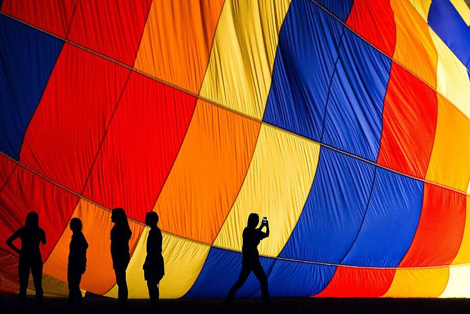 Participants are seen in silhouette as a balloon is inflated during the RE/MAX Ballunar Liftoff Festival Balloon Glow at the Johnson Space Center on Friday, Sept. 28, 2012, in Houston. Photo: Smiley N. Pool, Associated Press