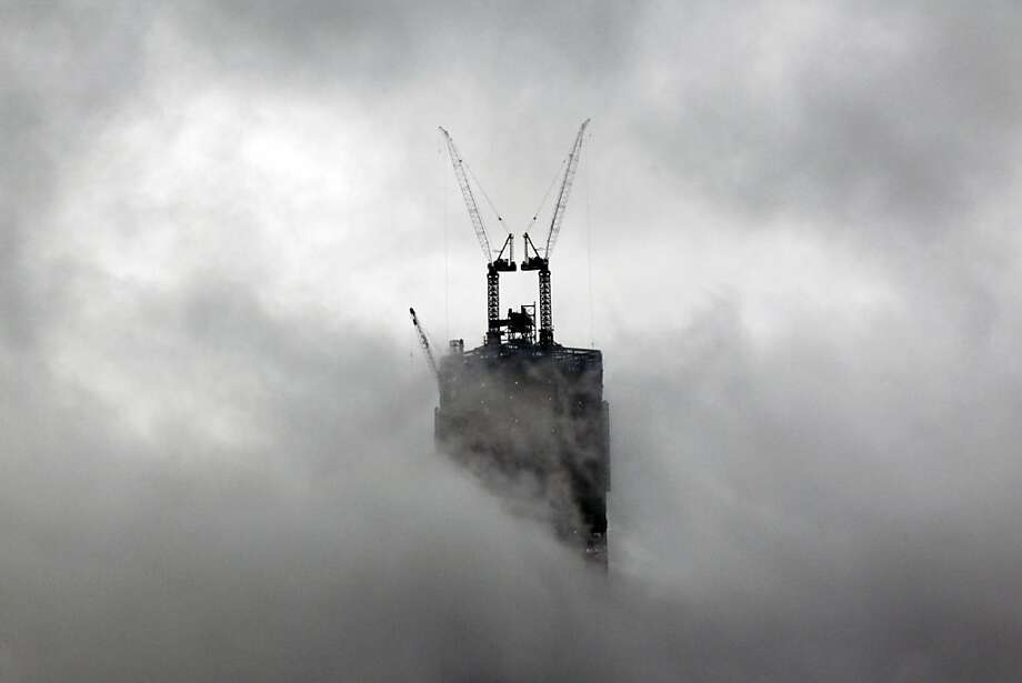 Construction cranes are seen from Jersey City, N.J., as they rise above clouds and rain at 1 World Trade Center in New York, Friday, Sept. 28, 2012. Photo: Mel Evans, Associated Press