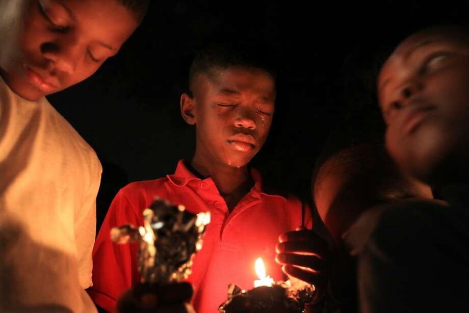 "Otis Keefer, left, and Ketevio Lee, center, both 11, participate in a vigil held for their friend and neighbor, Justin Thompson in Memphis, Tenn. Friday, Sept. 28, 2012.  ""Justin was my best friend,"" said Lee. Thompson, 15, was shot and killed by an off-duty Memphis Police Officer earlier this week. Photo: Nikki Boertman, Associated Press"