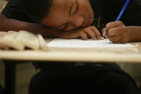 """Dana Gains, 11, works on his homework during quiet time at the end of the Manhood Development class at Edna Brewer Middle School on Wednesday Sep. 12, 2012 in Oakland, Calif. """"I thought this would be a better way to stay positive and be on task,"""" said Gains."""