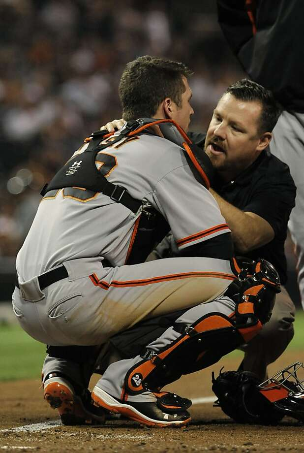 Trainer Dave Groeschner tends to Buster Posey, who was hit in the throat. Photo: Denis Poroy, Getty Images