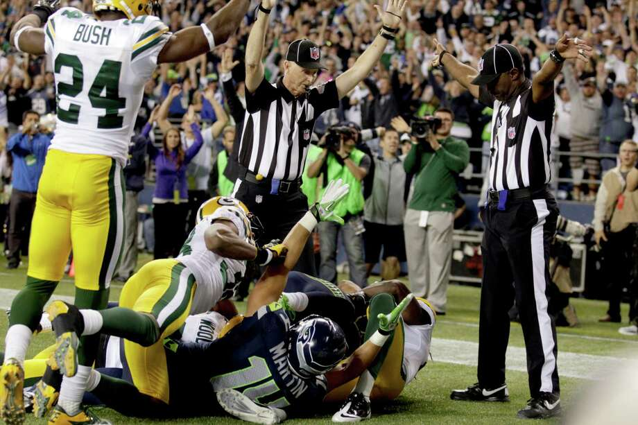 FILE - In this Monday, Sept. 24, 2012, file photo, an official, rear center, signals for a touchdown by Seattle Seahawks wide receiver Golden Tate, obscured, as another official, at right, signals a touchback, on the controversial last play of an NFL football game against the Green Bay Packers in Seattle. The Seahawks won 14-12. The NFL referee strike puts the spotlight on a nebulous notion that is often overlooked when it works as it's supposed to: the question of expertise. (AP Photo/Stephen Brashear, File) Photo: Stephen Brashear / FR159797 AP