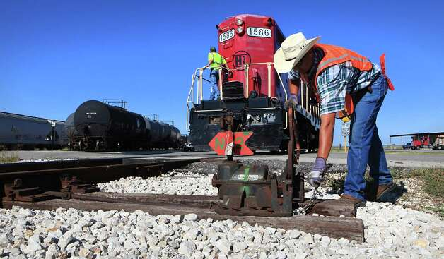 Hondo Railway worker Jarrett Persat switches a rail line as rail cars are moved in the yard.  The company has seen growth with the increased business from the Eagle Ford Shale oil production in south Texas.  Friday Sept. 21, 2012. Photo: BOB OWEN, San Antonio Express-News / © 2012 San Antonio Express-News