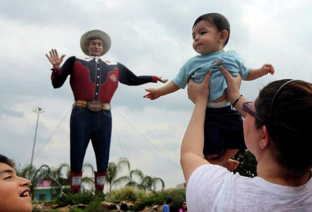 Six-month-old Baron Rodriguez, of Crandall, Texas, is held up by his mother Natasha Rodriguez for a photo with Big Tex as his brother Anthony Rodriguez, 11, looks on during the State Fair of Texas, Friday, Sept. 28, 2012, in Dallas. According to Natasha Rodriguez, she has held up each of her three children for a photo with Big Tex when they were infants. (AP Photo/LM Otero) Photo: LM Otero, Associated Press / AP