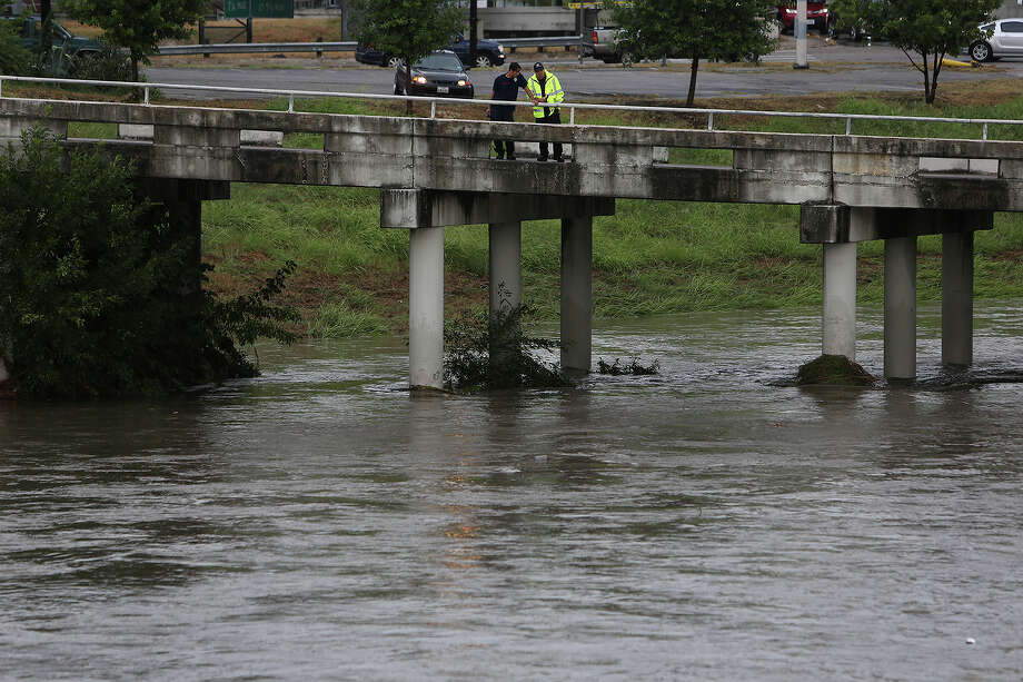 Emergency personnel stand watch over a drainage ditch next to the intersection of I-10 and Culebra near where a person was reported to be missing in the water after heavy rains in San Antonio on Thursday, Sept. 10, 2015. Photo: Lisa Krantz, SAN ANTONIO EXPRESS-NEWS / SAN ANTONIO EXPRESS-NEWS