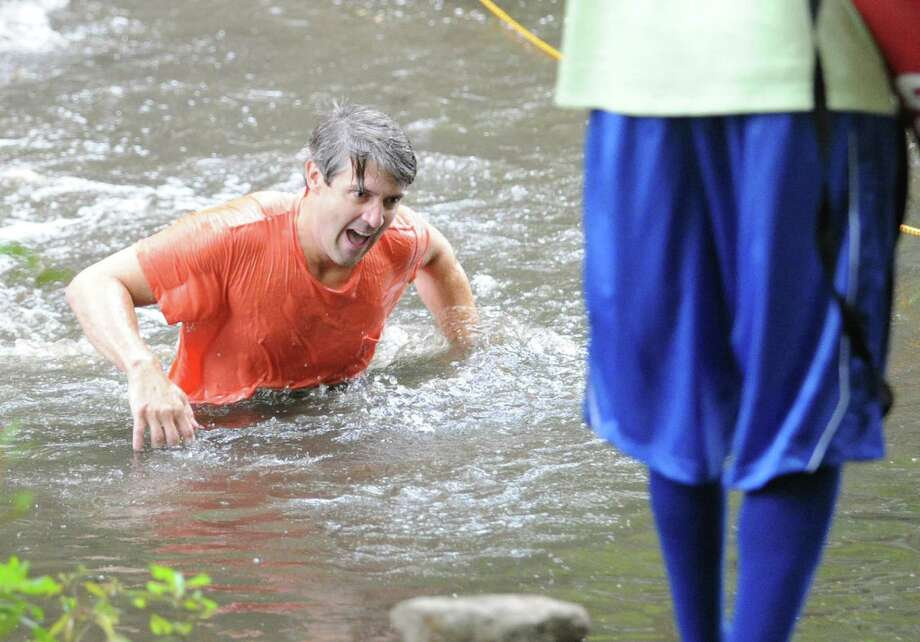 """John Pless wades across a stream while competing in the Boys & Girls Club of Greenwich """"Muddy Up 4 Kids"""" Mud Run at Camp Simmons in Greenwich, Saturday morning, Sept. 29, 2012. Photo: Bob Luckey / Greenwich Time"""