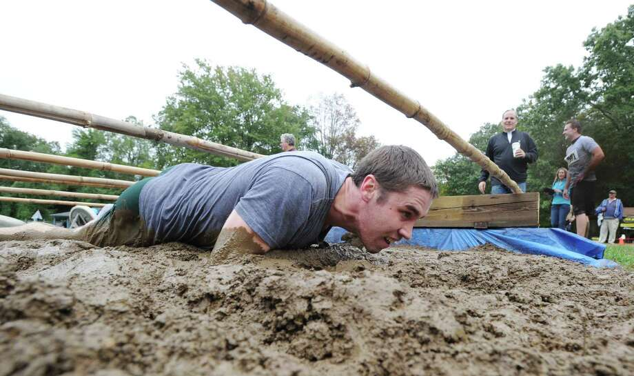 """A runner competes in the Boys & Girls Club of Greenwich """"Muddy Up 4 Kids"""" Mud Run at Camp Simmons in Greenwich, Saturday morning, Sept. 29, 2012. Photo: Bob Luckey / Greenwich Time"""