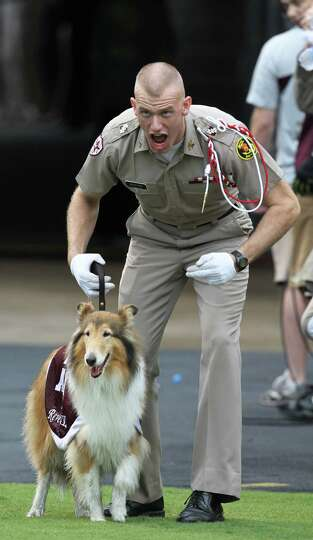 Texas A&M cadet Daylon Koster cheers with Reveille before the start of a college football game at Ky