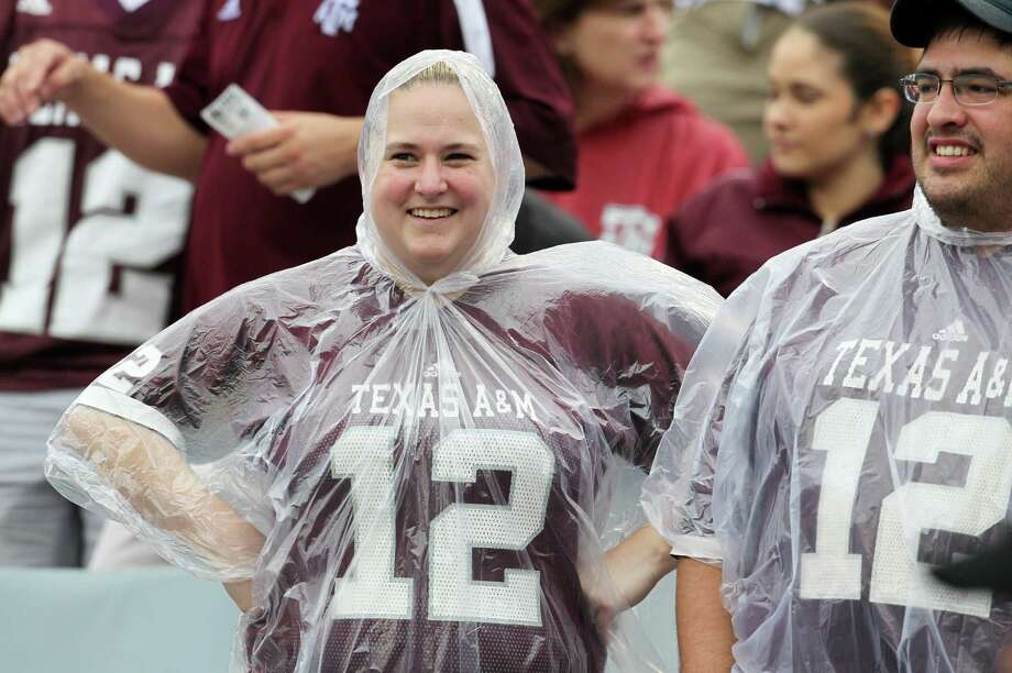 Texas A&M fans cover up during a slight drizzle during the first quarter of a college football game at Kyle Field, Saturday, Sept. 29, 2012, in College Station. Photo: Karen Warren, Houston Chronicle / © 2012  Houston Chronicle