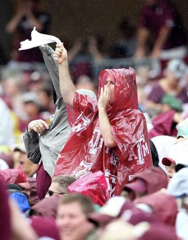 Texas A&M fans cover up from the drizzle as they cheer during the first half of a college football game at Kyle Field, Saturday, Sept. 29, 2012, in College Station. Photo: Karen Warren, Houston Chronicle / © 2012  Houston Chronicle