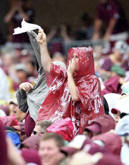 Texas A&M fans cover up from the drizzle as they cheer during the first half of a college football g