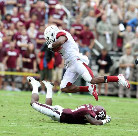 Arkansas running back Knile Davis (7) jumps over Texas A&M defensive back Toney Hurd Jr. (4) during the first half of a college football game at Kyle Field, Saturday, Sept. 29, 2012, in College Station. Photo: Karen Warren, Houston Chronicle / © 2012  Houston Chronicle