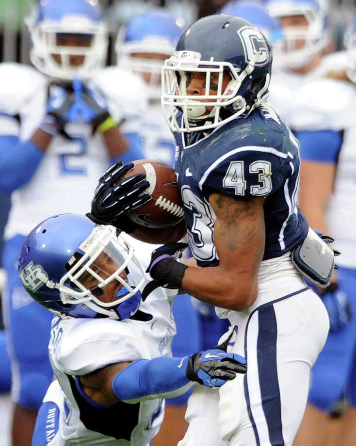 Connecticut's Lyle McCombs, right, eludes Buffalo's Najja Johnson during the first half of their NCAA college football game in East Hartford, Conn., on Saturday, Sept. 29, 2012. (AP Photo/Fred Beckham) Photo: Fred Beckham, Associated Press / Associated Press