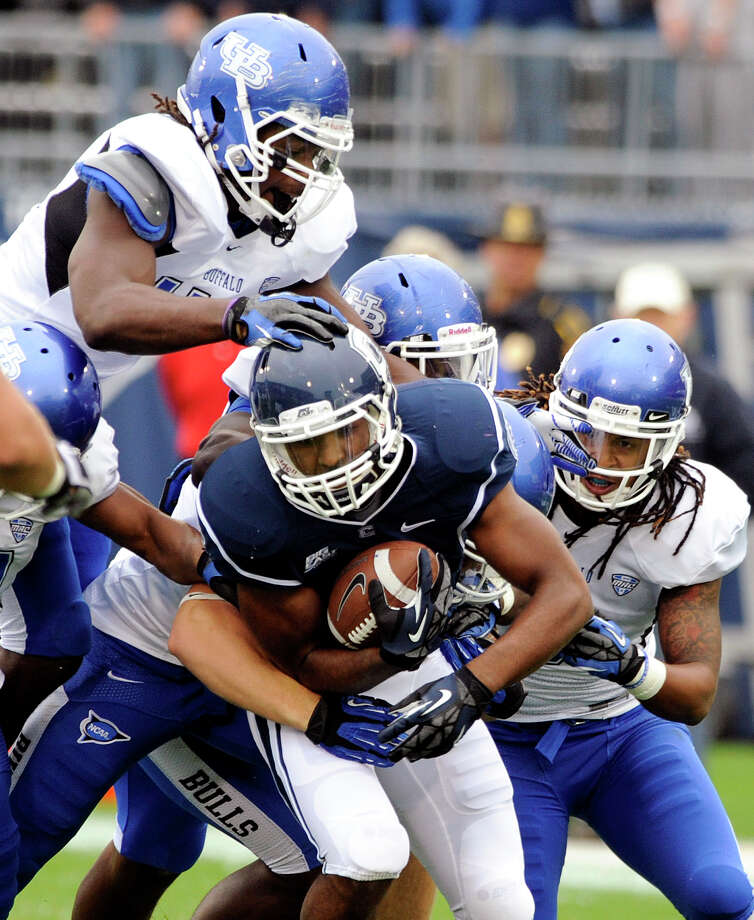 Connecticut's Lyle McCombs, center, is tackled by Buffalo defenders during the first half of their NCAA college football game in East Hartford, Conn., on Saturday, Sept. 29, 2012. (AP Photo/Fred Beckham) Photo: Fred Beckham, Associated Press / Associated Press