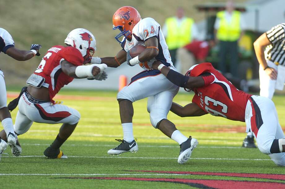 Lamar defensive back Jordan Garrett, left, and defensive end Jesse Dickson, right, combine for the stop on Langston University running back Ricky Shearin (24) during the first half at Provost Umphrey Stadium. Saturday, October 9, 2010 Valentino Mauricio/The Enterprise Photo: Valentino Mauricio / Beaumont