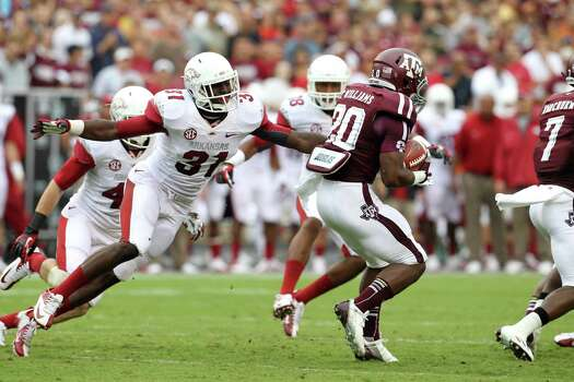 Texas A&M running back Trey Williams (20) gains yardage against Arkansas linebacker A.J. Turner (31) during the first quarter of a college football game at Kyle Field, Saturday, Sept. 29, 2012, in College Station. Photo: Karen Warren, Houston Chronicle / © 2012  Houston Chronicle